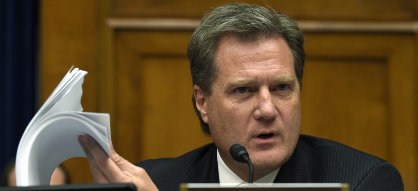 House Oversight and Government Reform Committee member Rep. Mike Turner, R-Ohio holds up a security form as he asks questions during the committee's hearing on recent cyber attacks at OPM, Wednesday, June 24, 2015, on Capitol Hill.