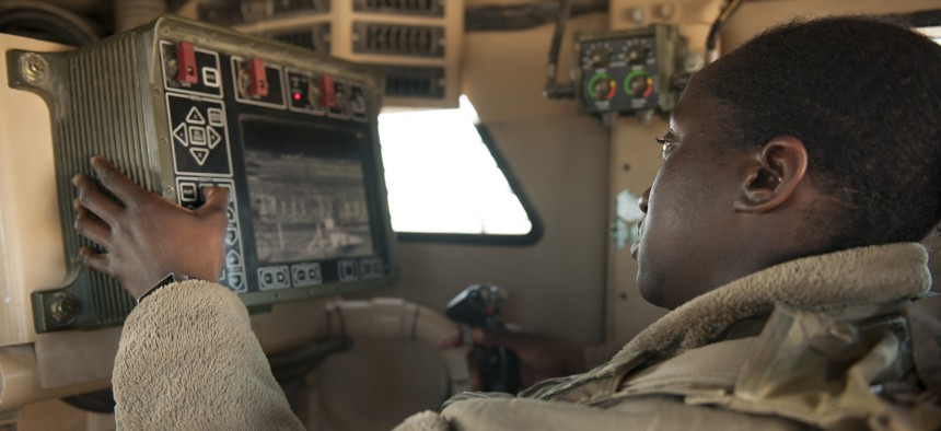 Senior Airman Amanda Nolan, 451st Expeditionary Support Squadron Security Forces Flight, scans a sector on a common remote operating weapons station from vehicle at Delta-1 Post on Kandahar Airfield, Afghanistan, January 20, 2016.
