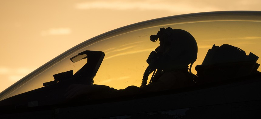 """At Bagram Air Base, Afghanistan, a U.S. Air Force F-16 Fighting Falcon """"Triple Nickel"""" aircraft pilot assigned to the 555th Expeditionary Fighter Squadron from Aviano Air Base, Italy, awaits weapons check, July 14, 2015."""