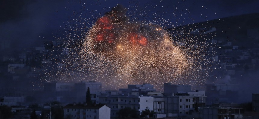 In this Oct. 20, 2014 file photo, thick smoke and flames erupt from an airstrike by the U.S.-led coalition in Kobani, Syria, as seen from a hilltop on the outskirts of Suruc, at the Turkey-Syria border.