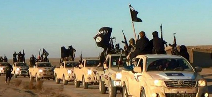 Members of the Islamic State hold up their weapons and wave its flags in a convoy on a road in Raqqa, Syria in this photo, released online in the summer of 2014 on a militant social media account.