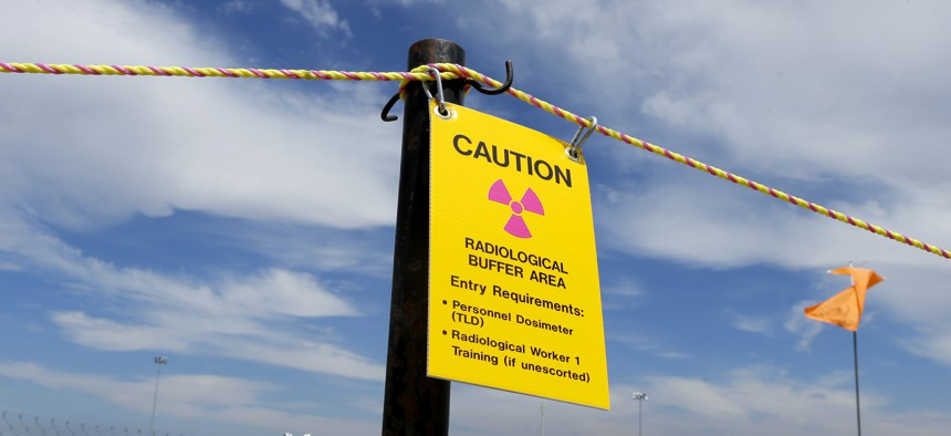 """A sign warns of radioactivity near a wind direction flag indicator at the """"C"""" tank farm on the Hanford Nuclear Reservation near Richland, Wash., July 9, 2014."""