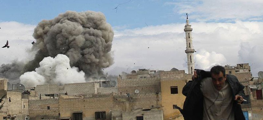 A Syrian man runs for cover from a Syrian government forces airstrike attack in Aleppo in this 2014 file photo.