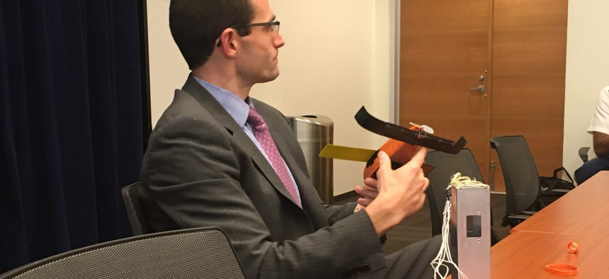 Will Roper, the director of the Strategic Capabilities Office, explains how the protective canister on the table protects the fourth-generation swarming Perdix drone in his hand as the micro-UAV deploys from a fighter jet's flare dispenser.