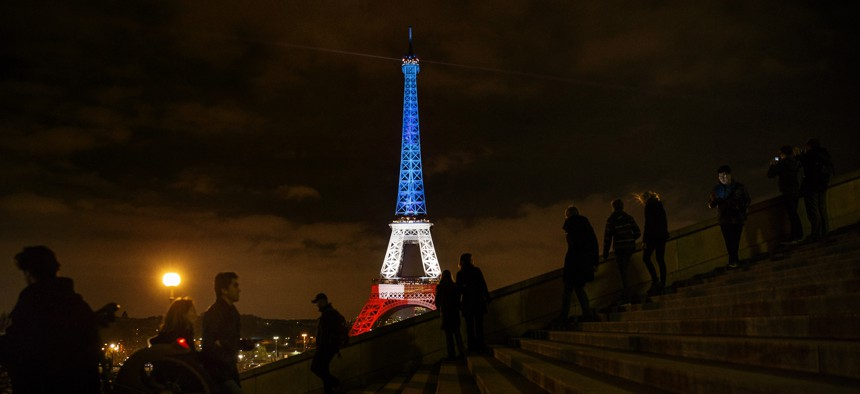 People walk and take pictures in front of the Eiffel Tower illuminated in the French colors in honor of the victims of the attacks on Friday in Paris, Monday, Nov. 16, 2015.