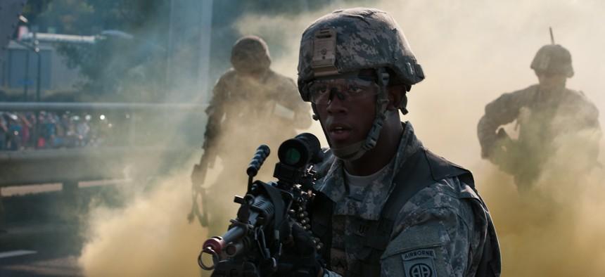 An 82nd Airborne Division paratrooper runs through smoke on during a reenactment of the bridge assault undertaken by the 504th Parachute Infantry Regiment in World War II during Operation Market Garden.
