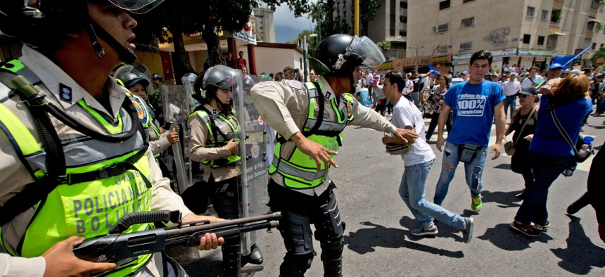 Bolivarian National Police officer try to disperse demonstrators during an opposition protest in Caracas, Venezuela, Friday, Sept. 16, 2016.