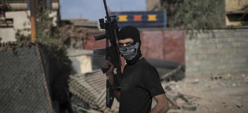A Iraqi special forces fighter walks with his rifle during flighting with Islamic State militants in eastern Mosul, Iraq, Sunday, Nov. 13, 2016.