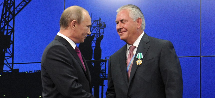 Russian President Vladimir Putin presents ExxonMobil CEO Rex Tillerson with a Russian medal at an award ceremony of heads and employees of energy companies at the St. Petersburg economic forum in St. Petersburg, Russia, June 21, 2012.