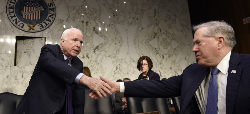 Senate Armed Services Committee Chairman Sen. John McCain, R-Ariz., left, shakes hands with Defense Undersecretary Frank Kendall, the military's chief weapons buyer, right, before the start of a hearing on Capitol Hill in Washington, Jan. 27, 2016.