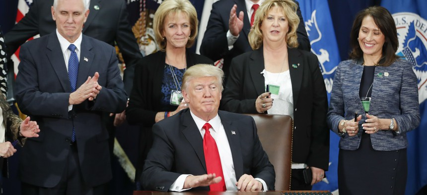 President Donald Trump, accompanied by Vice President Mike Pence and others, taps on the table after signing an executive order for immigration actions to build a border wall, Jan. 25, 2017, at the Department of Homeland Security in Washington.