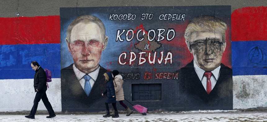 People walk by graffiti depicting the Russian President Vladimir Putin, left, and then-US President-elect Donald Trump, in Belgrade, Serbia, Jan. 20, 2017.