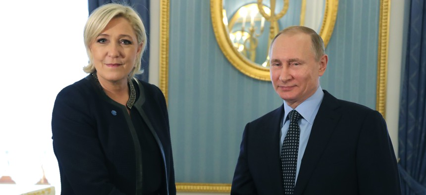 Russian President Vladimir Putin, right, shakes hands with French far-right presidential candidate Marine Le Pen, in the Kremlin in Moscow, Russia, Friday, March 24, 2017