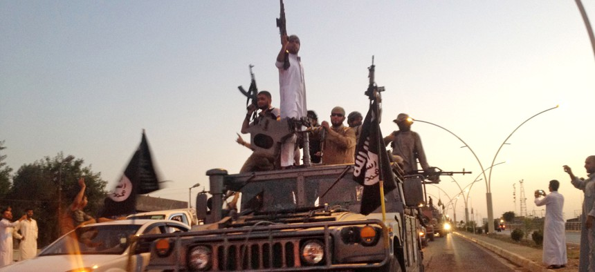 Islamic State fighters parade in a commandeered Iraqi security forces armored vehicle down a main road of Mosul, Iraq, when they controlled the city in 2014.
