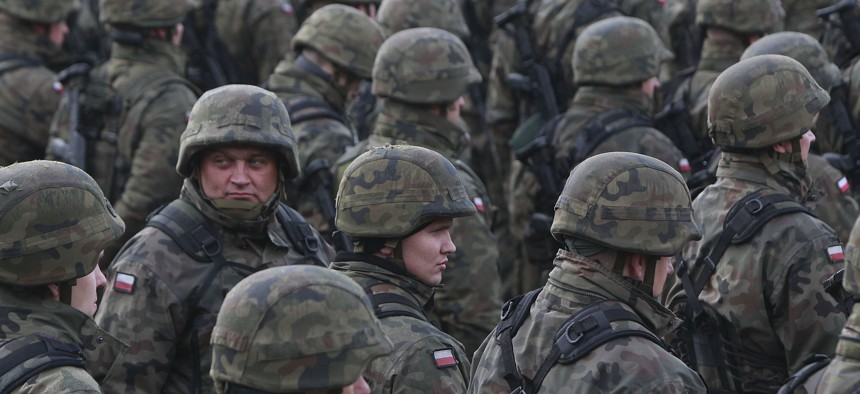 Polish soldiers attend a welcoming ceremony for U.S.-led NATO troops at polygon in Orzysz, northeastern Poland, Thursday, April 13, 2017.