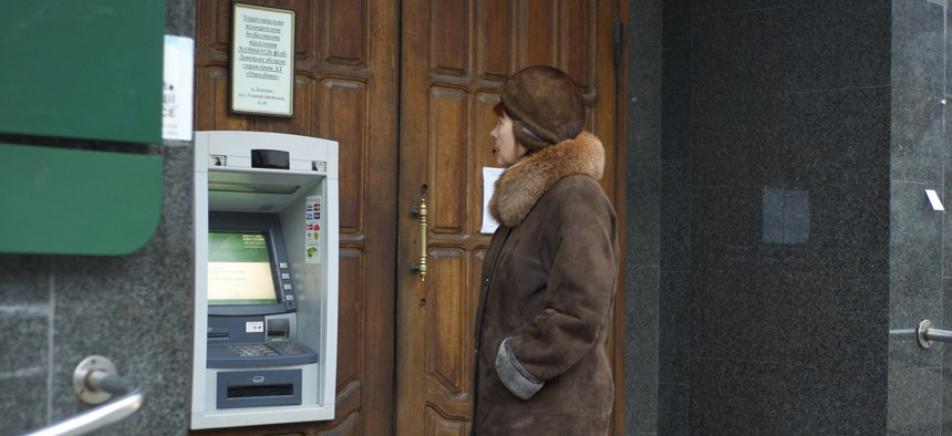 A woman stands at an ATM that doesn't work outside a Ukrainian bank in Donetsk, eastern Ukraine, Tuesday, Nov. 25, 2014.