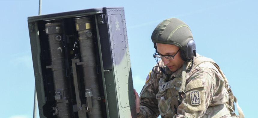 Spc. Bradley Muszalski, an air and missile defense crewmember with the 101st Airborne Division closes the door to an Avenger anti-aircraft missile launcher pod.