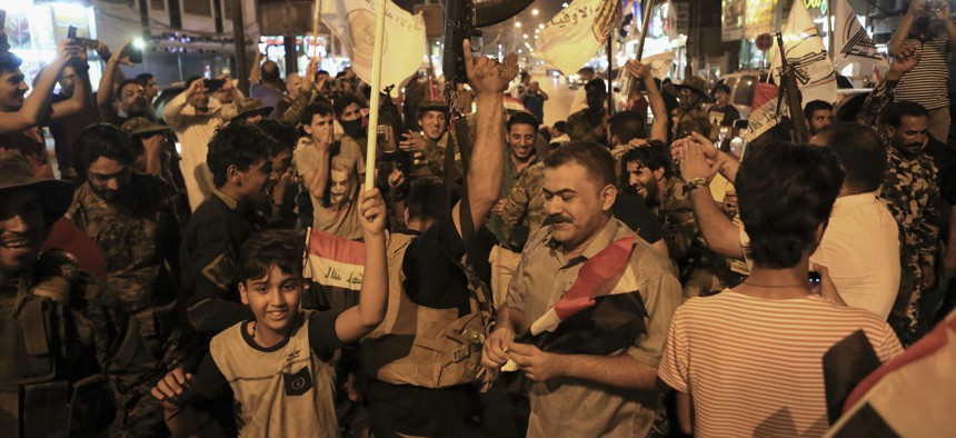 Iraqi security and civilians celebrate while holding national flags as they wait for the final announcement of the defeat of the Islamic state militants, in Basra, 340 miles (550 kilometers) southeast of Baghdad, Iraq, Sunday, July 9, 2017.