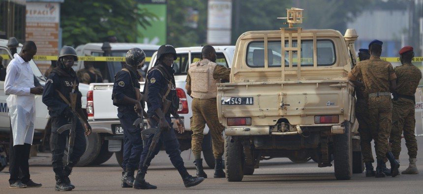 Security forces stand guard outside the site of a restaurant attacked in Ouagadougou, Burkina Faso, Monday, Aug. 14 , 2017. The death toll is still rising.