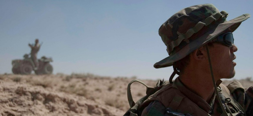 An Afghan special forces soldier scans the horizon as his American special forces counterpart reviews a map on an ATV in Kandahar province, June 2010.