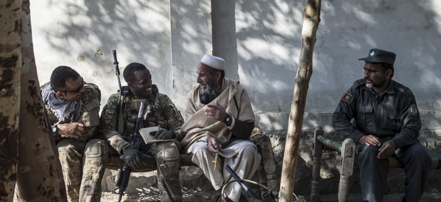 A U.S. Army soldier talks with an Afghan village elder during a key leader engagement outside of Camp Fenty, Afghanistan, Feb. 18, 2016.