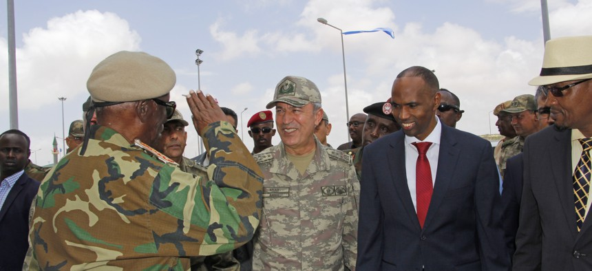 Turkish Chief of Staff General Hulusi Akar, second left, and Somali Prime Minister Hassan Ali Khayre, second right, receive a salute from a Somali soldier at combined Turkey-Somali training center during his visit to Mogadishu, Somalia, Sept. 30, 2017.