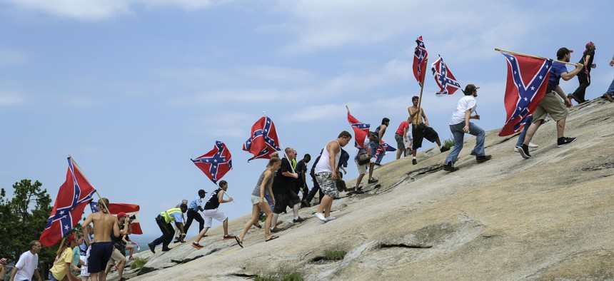 In this Aug. 1, 2015 file photo, Confederate flag supporters climb Stone Mountain to protest of what they believe is an attack on their Southern heritage during a rally at Stone Mountain Park in Stone Mountain, Ga.