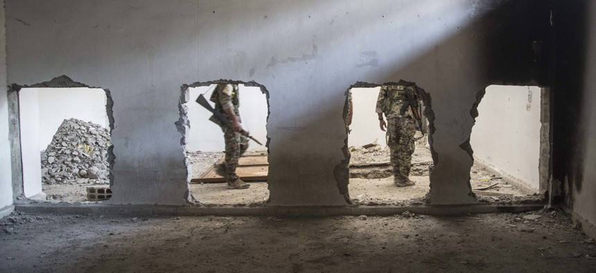 Members of the U.S.-backed Syrian Democratic Forces (SDF) walk inside the stadium that was the site of Islamic State fighters' last stand in the city of Raqqa, Syria, Friday, Oct. 20, 2017.