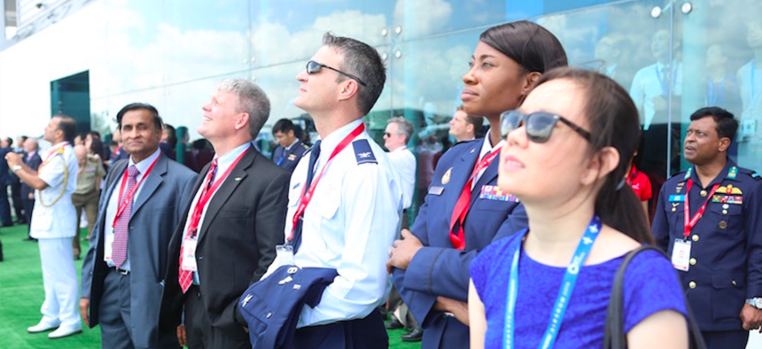 Attendees of the biennial regional event watch an air demonstration take place at the Singapore Airshow.