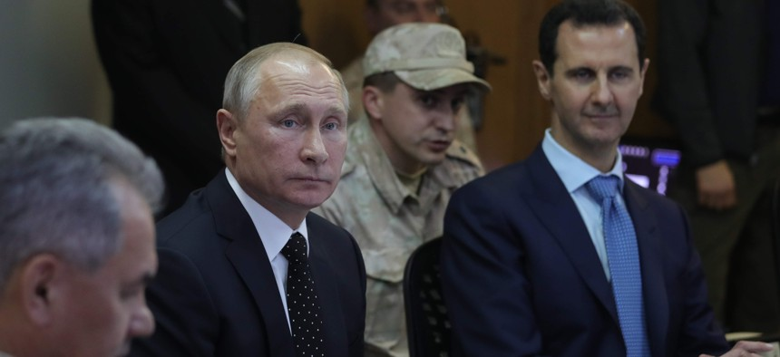 From left, Russian Defence Minister Sergei Shoigu, Russian President Vladimir Putin and Syrian President Bashar Assad attend a meeting at the Hemeimeem air base in Syria, on Monday, Dec. 11, 2017.
