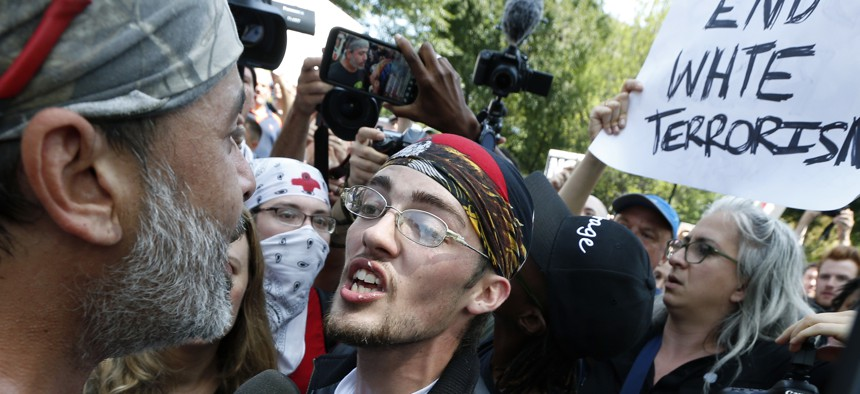 """In this Aug. 19, 2017 file photo, a supporter of President Donald Trump, center, argues with a counterprotester, left, at a """"Free Speech"""" rally by conservative activists on Boston Common in Boston."""
