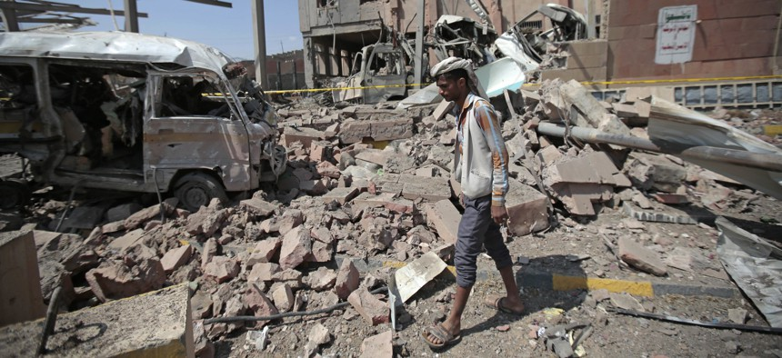 A man inspects rubble after a Saudi-led coalition airstrike in Sanaa, Yemen, Sunday, Feb. 4, 2018.