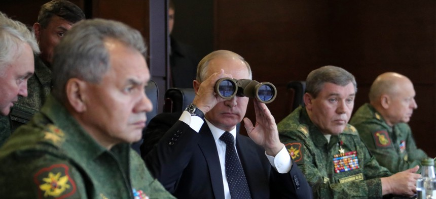 Russian President Vladimir Putin, center, Defence Minister Sergei Shoigu, left, and Chief of the General Staff of the Russian Armed Forces Valery Gerasimov, second right, watch a military exercise at a training ground at the Luzhsky Range. Sept, 2017.