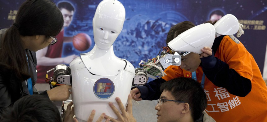 , Chinese students work on the Ares, a humanoid bipedal robot designed by them with fundings from a Shanghai investment company, displayed during the World Robot Conference in Beijing. Photo taken October 21, 2016