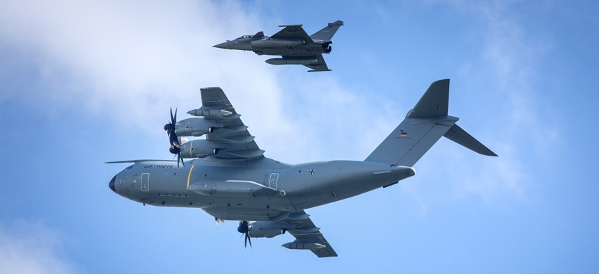 A German Air Force Airbus A400M and two fighter jets during the 2018 International Aerospace Exhibition.