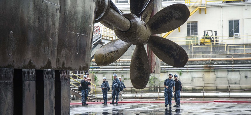Sailors assigned to the submarine tender USS Frank Cable (AS 40) see their ship's propeller for the first time, as she drains in dry-dock, in Portland, Ore.