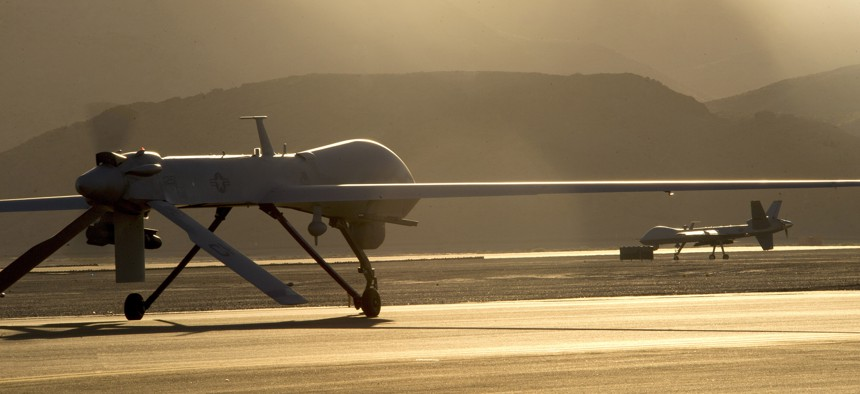 An MQ-1B Predator, left, and an MQ-9 Reaper taxi to the runway in preparation for takeoff June 13, 2014, at Creech Air Force Base, Nev.