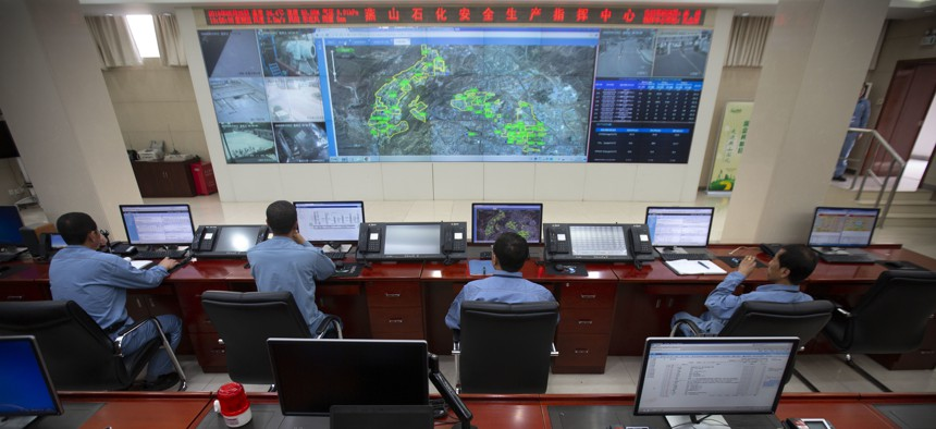 Workers sit at computer terminals as they monitor a large display screen in the command center at the Sinopec Yanshan Petrochemical Company on the outskirts of Beijing, Friday, May 25, 2018.