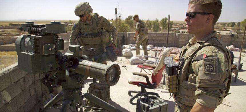 U.S. Army soldiers stands next to a a guided-missile launcher, a few miles from the frontline, in the village of Abu Ghaddur, east of Tal Afar, Iraq, Sunday, Aug. 20, 2017.