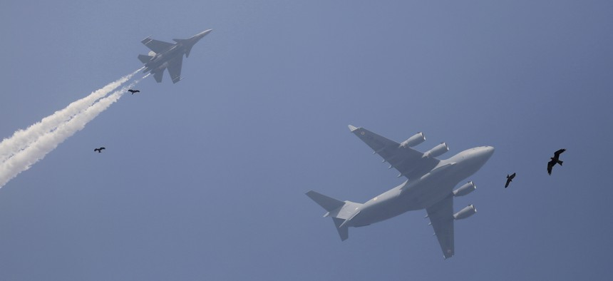 Birds fly past as Indian Air Force Sukhoi fighter jet, left, and Indian Air Force C-17 Globemaster display a fly-by during the rehearsals ahead of annual Republic Day parade in New Delhi, India, Thursday, Jan. 18, 2018.