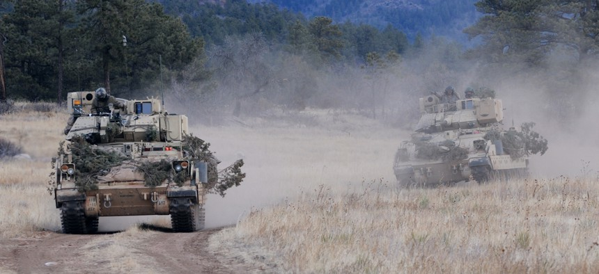 Soldiers from the U.S. Army's 4th Infantry Division drive their M3A3 Bradley Fighting Vehicles to reach a phase line where they will move into a defensive posture during platoon scout training near Fort Carson's Camp Red Devil, Jan. 26, 2013.
