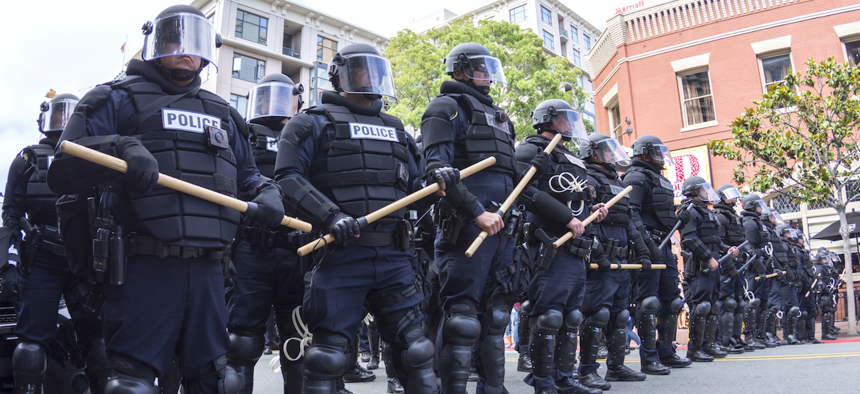 Riot police in full tactical gear stand ready to confront protesters at a Trump rally at the San Diego Convention Center on May 27, 2016.