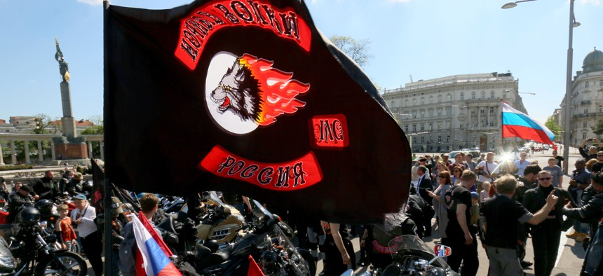 Members and supporters of the Russian motorcycle club Night Wolves arrive at the heroes' monument of the Red Army, background left, in downtown Vienna, Austria, Friday, May 6, 2016.