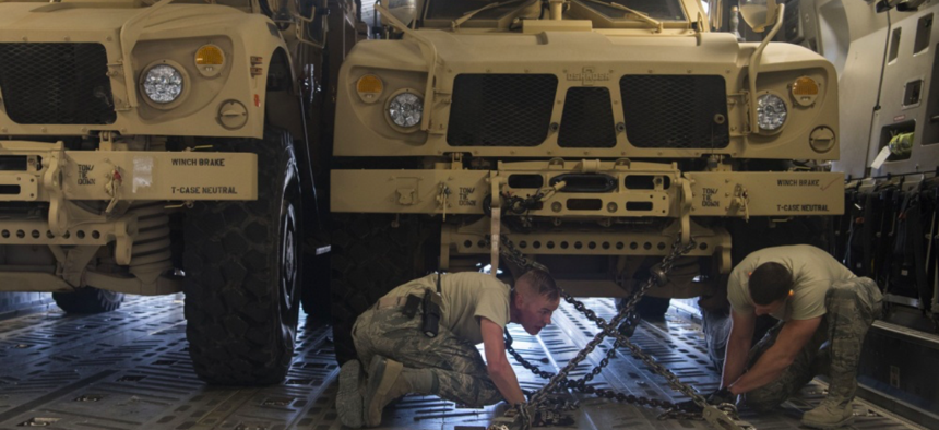 Tech. Sergeants Josiah Bourke and Nick Akins, 332nd Expeditionary Logistics Readiness Squadron air transportation specialists, secure mine-resistant ambush protected vehicles for transportation in Southwest Asia March 7, 2018.