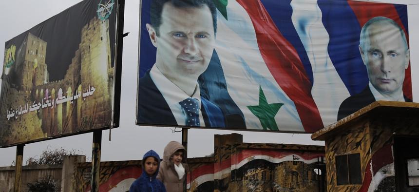 yrian walk by posters of Syrian President Bashar Assad and Russian President Vladimir Putin in Aleppo, Syria, Thursday, Jan. 18, 2018.