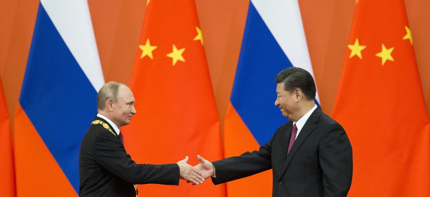 In this June 8, 2018, file photo, Chinese President Xi Jinping, right, and Russian President Vladimir Putin shake hands during an awarding ceremony at the Great Hall of the People in Beijing, China.