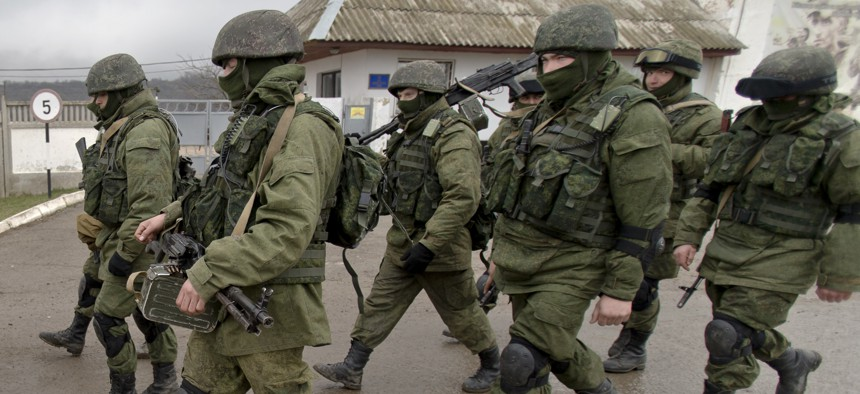 In this March 20, 2014 file photo Pro-Russian soldiers march outside an Ukrainian military base in Perevalne, Crimea.