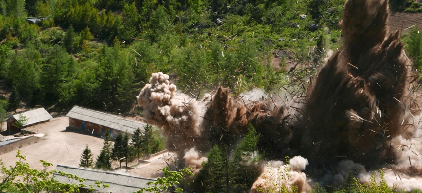 In this Thursday, May 24, 2018 photo, smoke and debris rise in the air as barracks buildings for guards and tunneling workers at North Korea's nuclear test site are blown up at Punggye-ri, North Hamgyong Province, North Korea