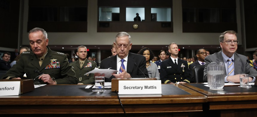 Defense Secretary Jim Mattis, center, flanked by Joint Chiefs Chairman Gen. Joseph Dunford, left, and Defense Undersecretary David Norquist, prepares to testify June 13, 2017, before a Senate Armed Services Committee.