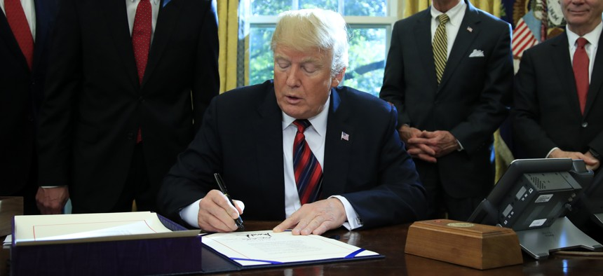 """President Donald Trump signs the """"America's Water Infrastructure Act of 2018"""" into law during a ceremony in the Oval Office at the White House in Washington, Tuesday, Oct. 23, 2018."""